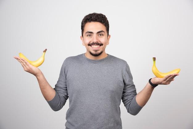 Um jovem segurando duas bananas frescas.