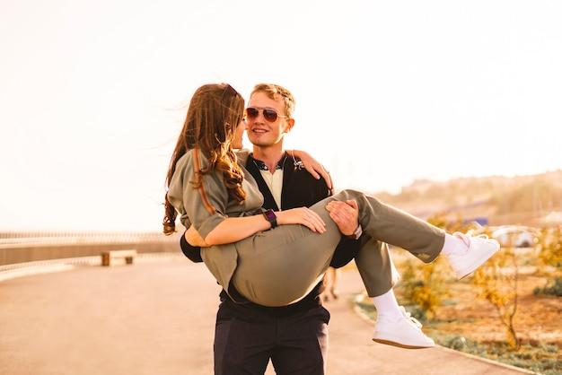 Um jovem segurando e carregando sua jovem namorada na rua, se abraçando e se divertindo casal