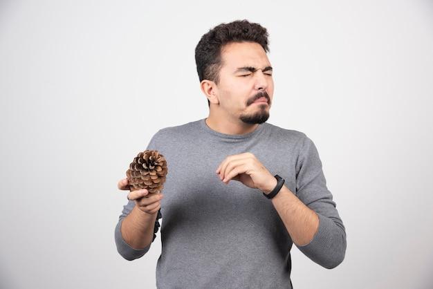 Um jovem segurando nas mãos uma grande pinha.
