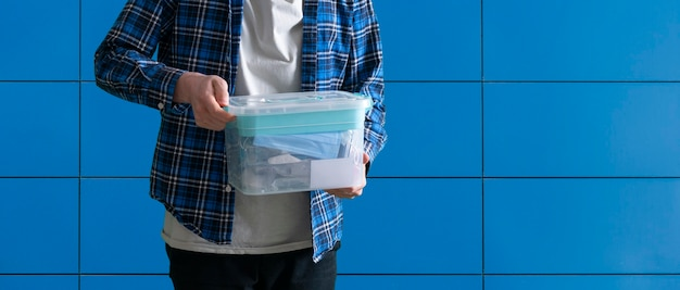 Um jovem segurando uma caixa de plástico com coisas armazenadas dentro