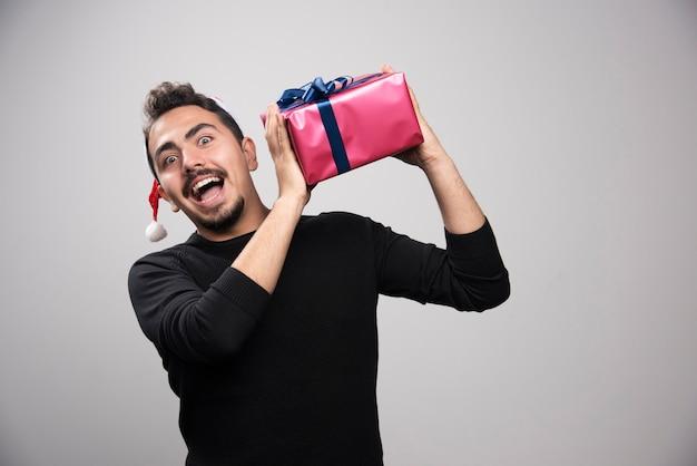 Um jovem segurando uma caixa de presente sobre uma parede cinza.