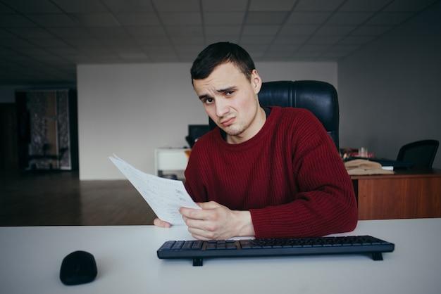 Um jovem senta-se em uma cadeira de escritório, segurando um papel e olha perplexo para a câmera.