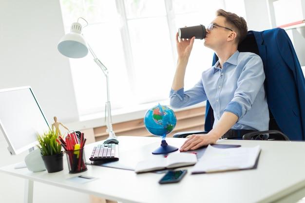 Um jovem senta-se no escritório em uma mesa de computador, detém um globo com a mão e bebe café.
