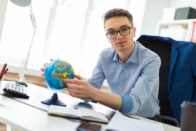Um jovem senta-se no escritório em uma mesa de computador e detém um globo em suas mãos.