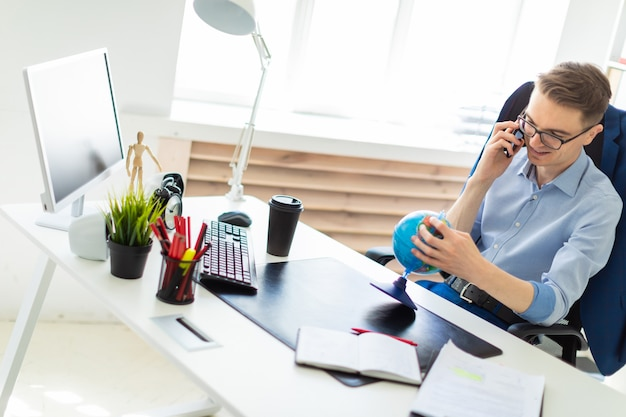 Um jovem senta-se no escritório em uma mesa de computador, falando ao telefone e olhando para o globo.