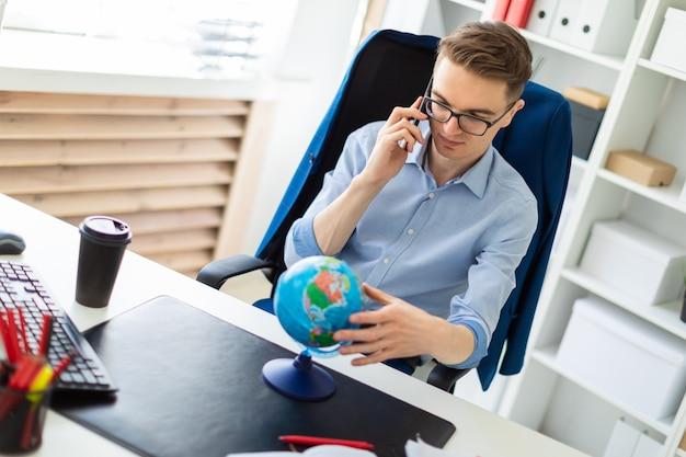 Um jovem senta-se no escritório em uma mesa de computador