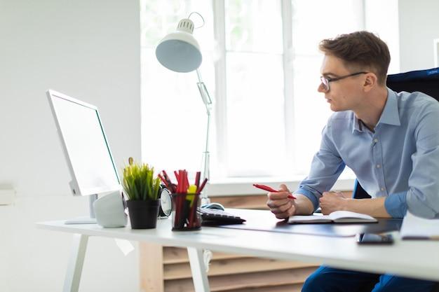 Um jovem senta-se no escritório, na mesa do computador, segura uma caneta na mão e olha para o monitor.