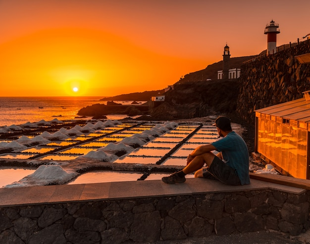 Um jovem sentado ao pôr do sol do farol de fuencaliente ao lado da mina de sal, na rota dos vulcões ao sul da ilha de la palma, nas ilhas canárias, espanha