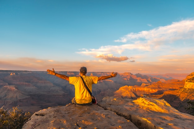 Um jovem sentado com as mãos abertas e vestindo uma camisa amarela no pôr do sol no powell point do grand canyon. arizona