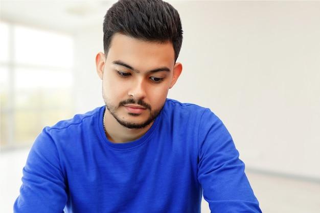 Um jovem sentado em um laptop em busca de trabalho, fazendo negócios na internet. na luz