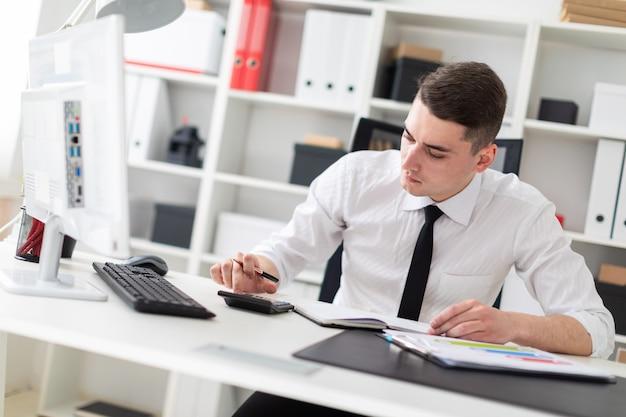 Um jovem sentado em uma mesa de computador no escritório e trabalhando com documentos.