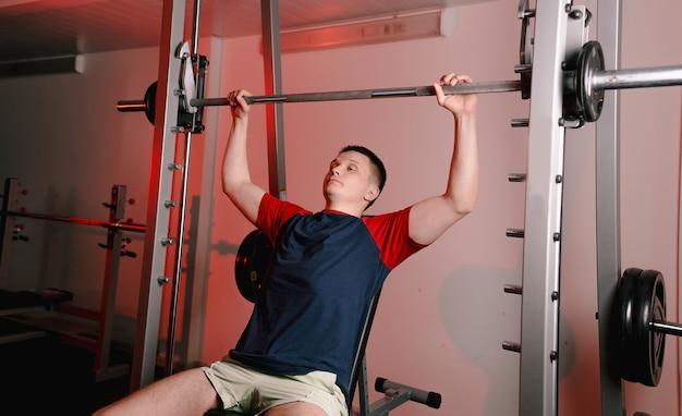 Um jovem sentado levanta uma barra na academia durante um treino de peito. estilo de vida saudável. ginásio moderno