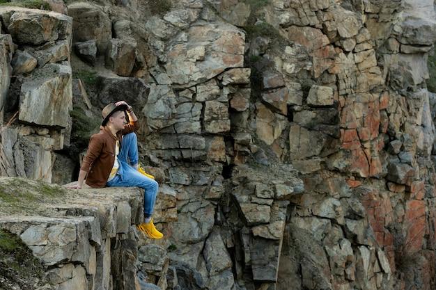 Um jovem sentado nas montanhas de primavera ao pôr do sol e apreciando a vista da natureza. viagem pela montanha e pela costa, liberdade e estilo de vida ativo, observando a paisagem