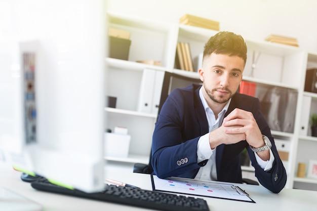 Um jovem sentado no escritório em uma mesa de computador e trabalhando com documentos.