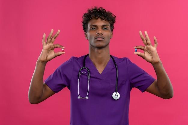 Um jovem sério, bonito, de pele escura, cabelo encaracolado, uniforme violeta e estetoscópio segurando comprimidos