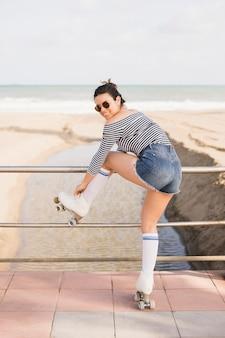 Um jovem skatista feminino atraente, amarrando o laço de patins na praia