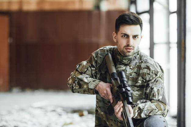 Um jovem soldado militar está sentado com um grande rifle nas mãos, perto da janela de um prédio desabado