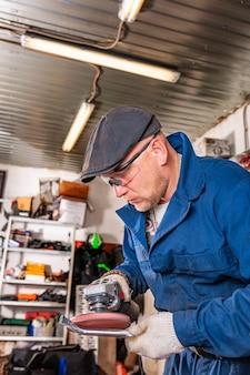 Um jovem soldador com uma camiseta azul, óculos e luvas de construção processa uma rebarbadora de metal na garagem