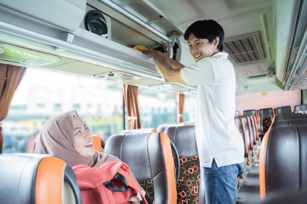 Um jovem sorri enquanto ajuda uma mulher com um lenço na cabeça a colocar sua bolsa em uma prateleira enquanto está de pé no ônibus