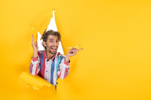Um jovem sorridente feliz e emocionado posa em um buraco de papel amarelo rasgado no fundo