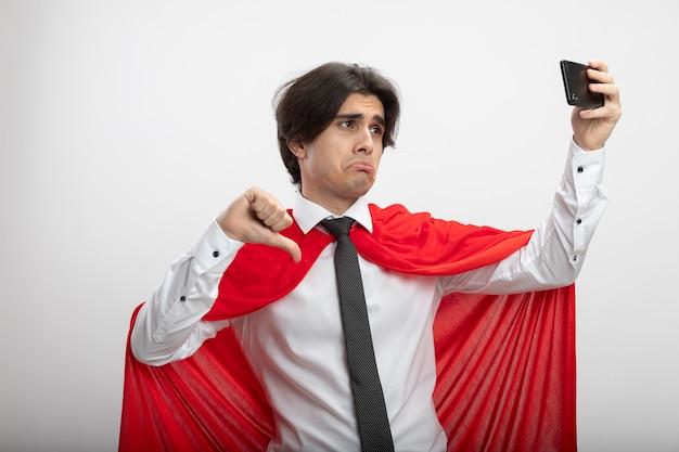 Um jovem super-herói triste usando gravata tira uma selfie e mostra o polegar para baixo, isolado no fundo branco