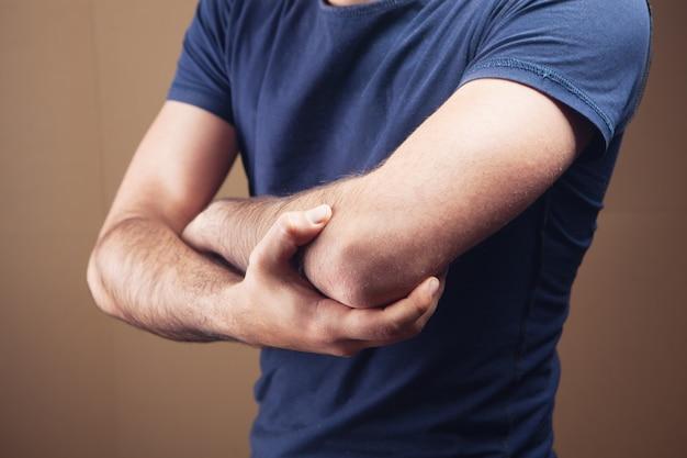 Um jovem tem um cotovelo dolorido