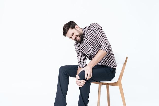 Um jovem tem uma dor na perna. ele massageia uma perna.
