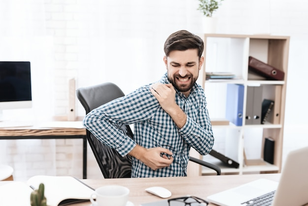Um jovem tem uma dor no ombro.