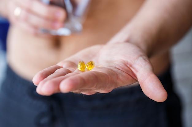 Um jovem tem vitaminas e um copo de água nas mãos. pílulas de imunidade