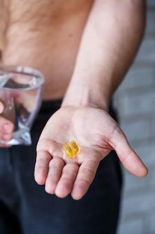 Um jovem tem vitaminas e um copo de água nas mãos. pílulas de imunidade Foto Premium