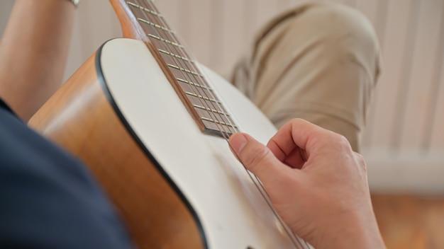 Um jovem tocando violão em casa