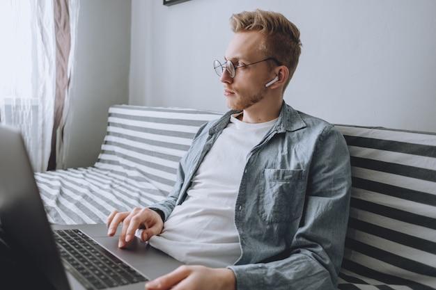 Um jovem trabalha em casa com um laptop.