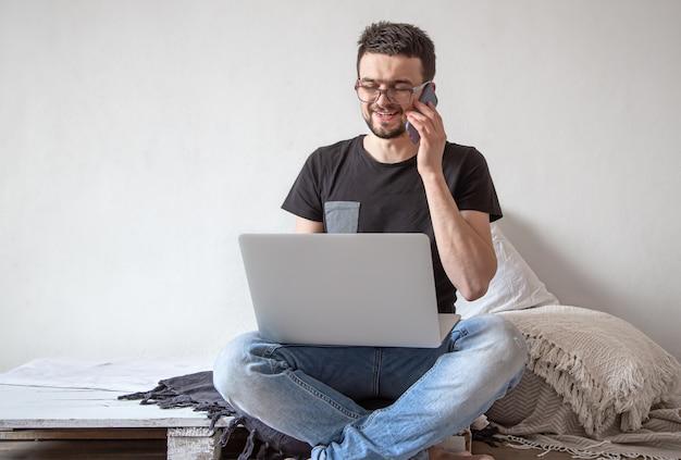 Um jovem trabalha remotamente atrás de um laptop em casa, na parede interna da sala de luz. conceito de freelance e internet.
