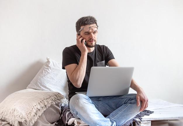 Um jovem trabalha remotamente em um computador em casa.