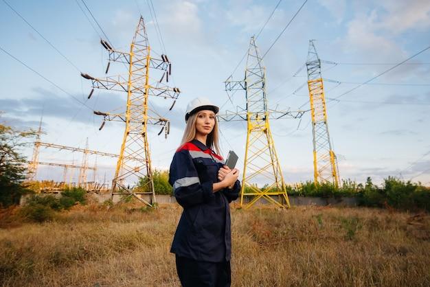 Um jovem trabalhador de engenharia inspeciona e controla o equipamento da linha de energia. energia.