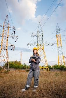 Um jovem trabalhador de engenharia inspeciona e controla o equipamento da linha de energia