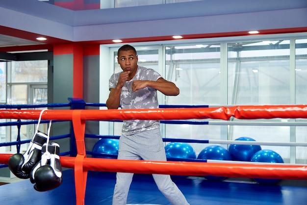 Um jovem treina no ringue de boxe no ginásio.
