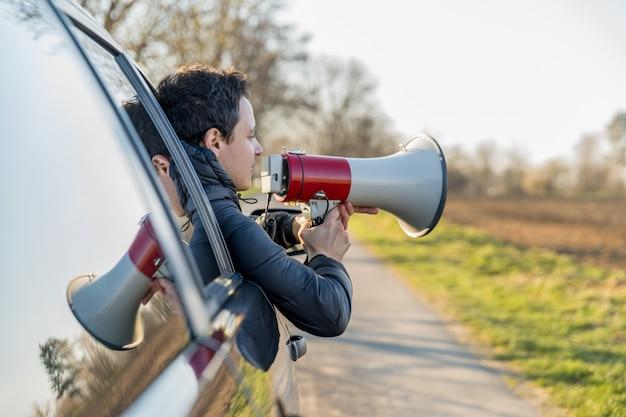 Um jovem trouxe ao megafone notícias importantes através da janela de um carro