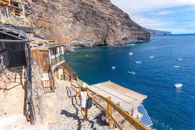 Um jovem turista descendo as escadas para chegar à enseada de puerto de puntagorda, ilha de la palma, nas ilhas canárias. espanha