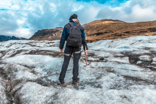 Um jovem turista no gelo da geleira svinafellsjokull. islândia