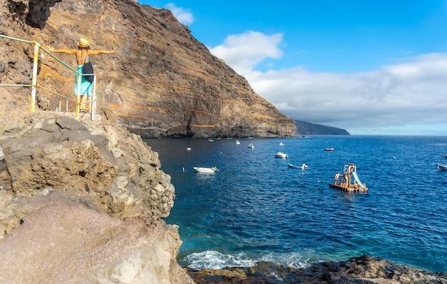 Um jovem turista no verão do ponto de vista olhando e apreciando a enseada de puerto de puntagorda, ilha de la palma, nas ilhas canárias. espanha