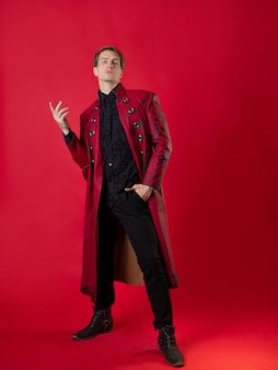 Um jovem ultrajante em um casaco vermelho ousado em um estilo noir vintage, poses épicas e faz um gesto com a mão. foto em um fundo vermelho