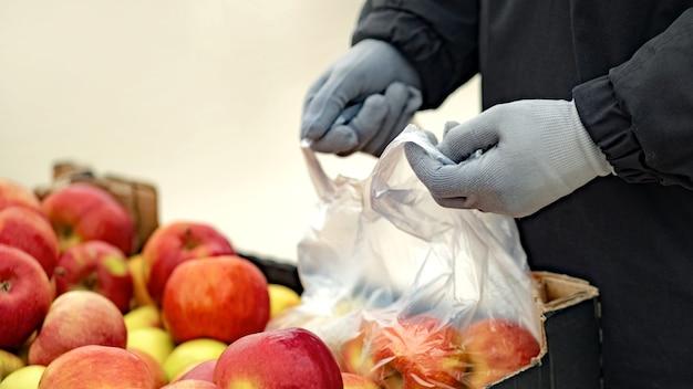 Um jovem usando luvas de proteção compra comida em uma loja durante a epidemia de coronavírus