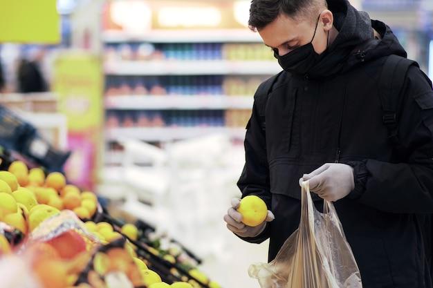 Um jovem usando máscara e luvas de proteção compra comida em uma loja durante a epidemia de coronavírus