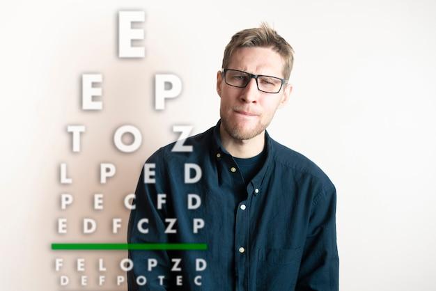 Um jovem verifica a visão, examina a saúde com o gráfico de letras de teste