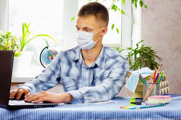 Um jovem, vestido com uma camisa xadrez e uma máscara esterilizada, se senta à mesa e olha para um laptop. conceito de educação. situação epidemiológica precária.