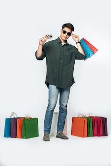 Um jovem vestindo uma camisa escura e jeans carregava várias sacolas para fazer compras com cartão de crédito