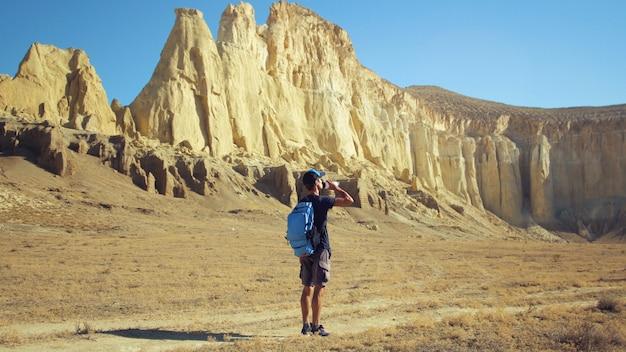Um jovem viajante bebe água contra as rochas