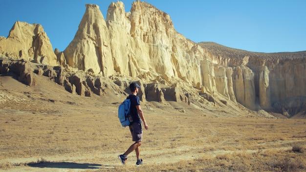 Um jovem viajante caminha ao longo de um caminho em uma área montanhosa