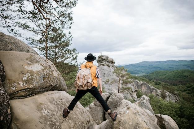 Um jovem viajante moderno fica entre duas rochas e olha para longe